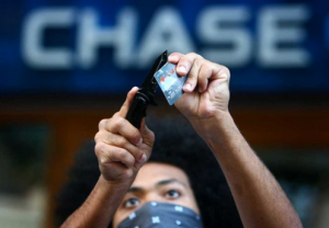 "A protester cuts up a bank card during the ""Occupy Seattle"" protest in front of Chase Bank on 4th Avenue Saturday, October 15, 2011 in Seattle. About 5,000 people joined protesters camped at Westlake Park for two weeks. The demonstration was an offshoot of the Occupy Wall Street protest in New York and dubbed as a global day of action by the movement."