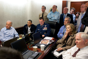 "U.S. President Barack Obama and Vice President Joe Biden, along with members of the national security team, receive an update on Operation Neptune's Spear, a mission against Osama bin Laden, in one of the conference rooms of the Situation Room of the White House, May 1, 2011. They are watching live feed from drones operating over the bin Laden complex. Seated, from left to right, are: Vice President Biden, President Obama, Brigadier General Marshall B. ""Brad"" Webb, USAF, Assistant Commanding General, Joint Special Operations Command; Denis McDonough, Deputy National Security Advisor; Hillary Rodham Clinton, Secretary of State; and Robert Gates, Secretary of Defense. Standing, from left to right, are: Admiral Mike Mullen, USN, Chairman of the Joint Chiefs of Staff; Tom Donilon, National Security Advisor ; Bill Daley, Chief of Staff; Tony Blinken, National Security Advisor to the Vice President; Audrey Tomason, Director for Counterterrorism; a person in a beige shirt (only part of the shoulder is visible); John Brennan, Assistant to the President for Homeland Security and Counterterrorism; James Clapper, Director of National Intelligence; and a person in a black suit with a white tie, similar to the one seen here. Note: a classified document in front of Hillary Clinton has been obscured by the White House."